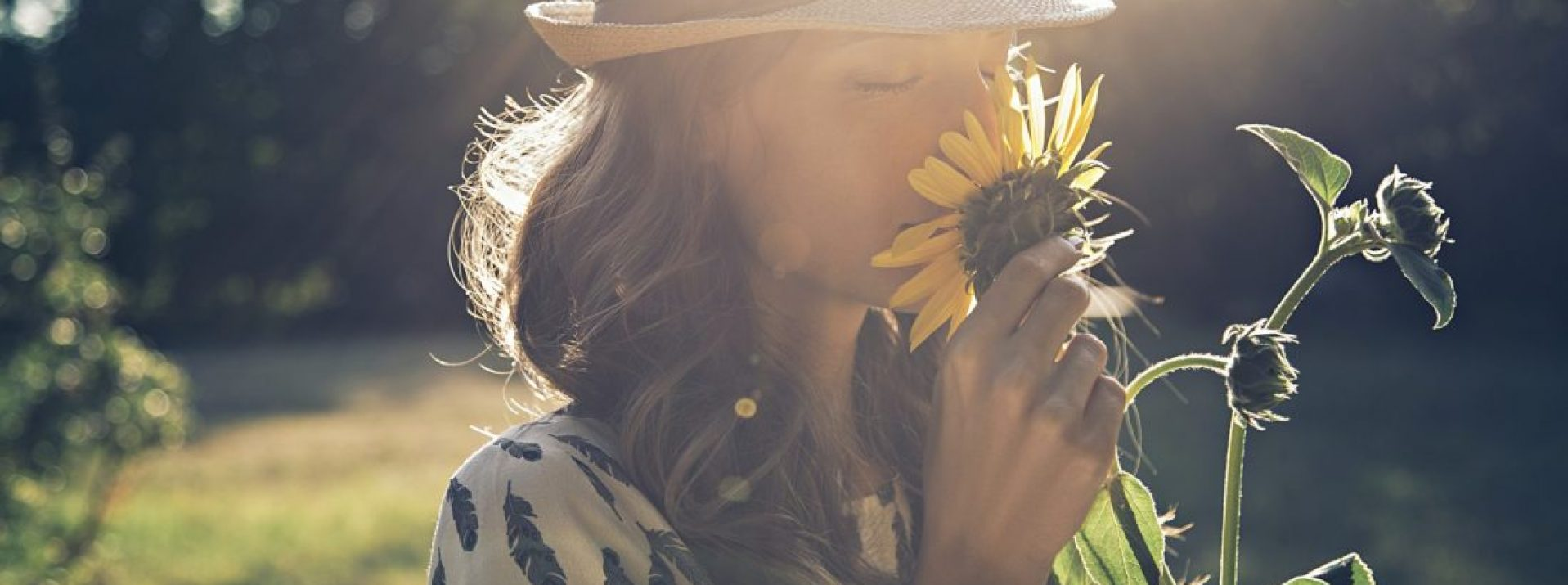 Girl smells sunflower in nature